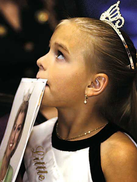 Little Miss Amarillo Haley Ann Lynn, 8, Amarillo, looks toward one of her mother's friends while holding a fan of Miss Amarillo Brooke Staudt in Amarillo during a Thursday June 21, 2001, bon voyage event for Staudt. Staudt is scheduled to participate in the Miss Texas Pageant, which will be in Fort Worth on July 7. (Photo by Michael Lemmons) NR2-EA-LIFESTYLES/PAGEANT2-ML.CMYK